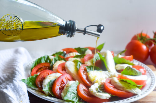 Extra virgin olive oil being drizzled on a freshly made caprese salad on a white plate.