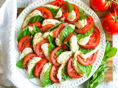 Caprese Salad | Keto, Low-Carb - Photo of a Caprese Salad arranged on a white plate atop a wooden cutting board - ready to serve.