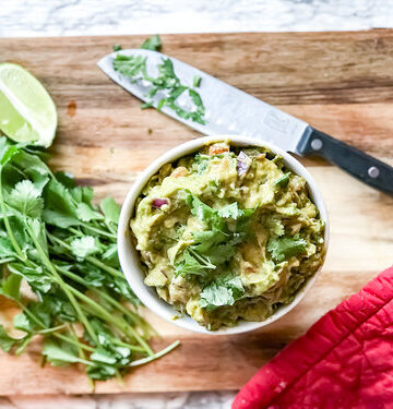Guacamole in a white bowl next to cilantro and lime on a cutting board