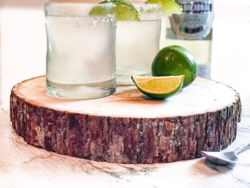 Easy Keto Low-Carb Margarita by AGirlCalledAdri photographed with a cut lime atop cutting board.
