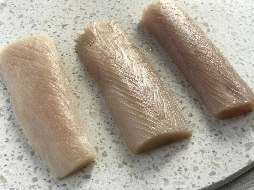 Raw mahi mahi on a white cutting board