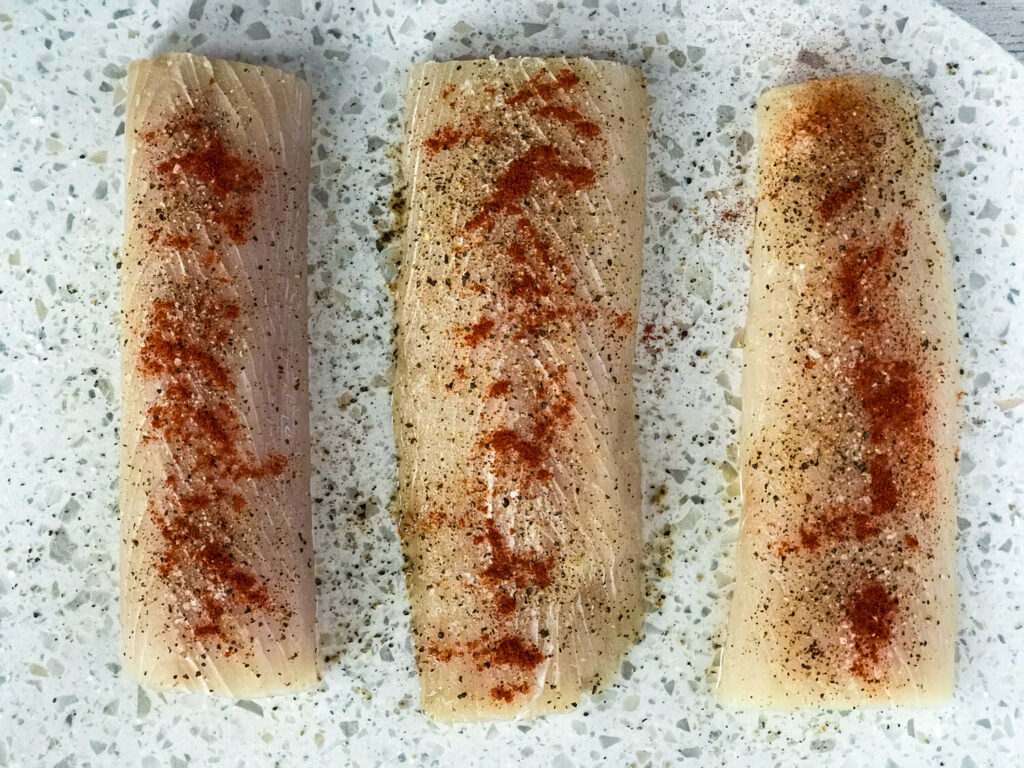 Raw and seasoned mahi mahi on a white cutting board.