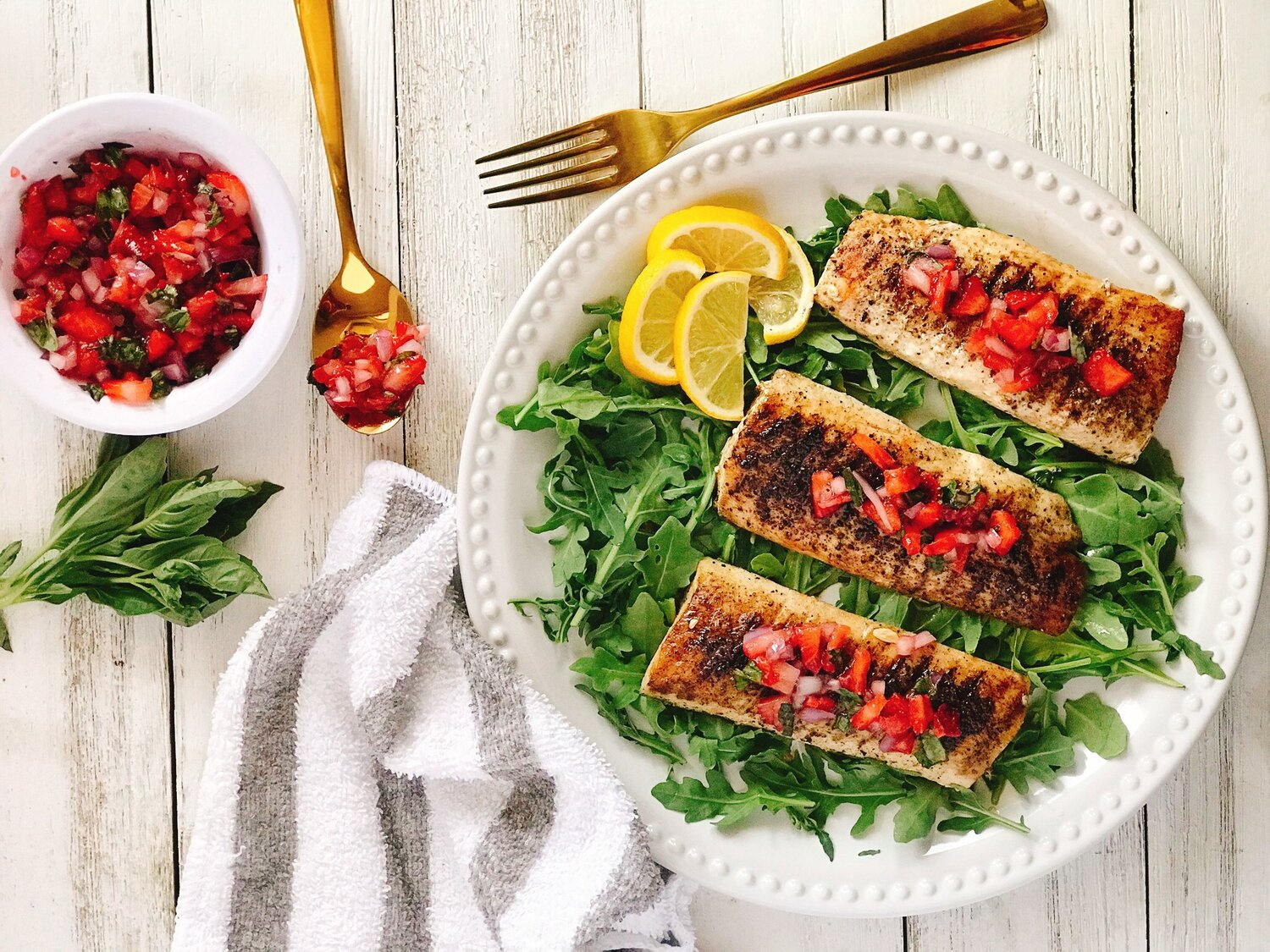 grilled mahi mahi on white plate topped with strawberry salsa