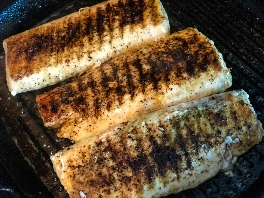 cooked maho mahi in a black cast iron grill pan