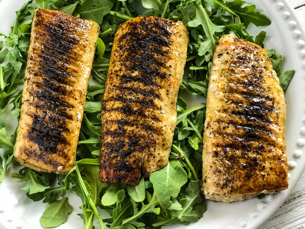 grilled mahi mahi on a bed of arugula on a white plate