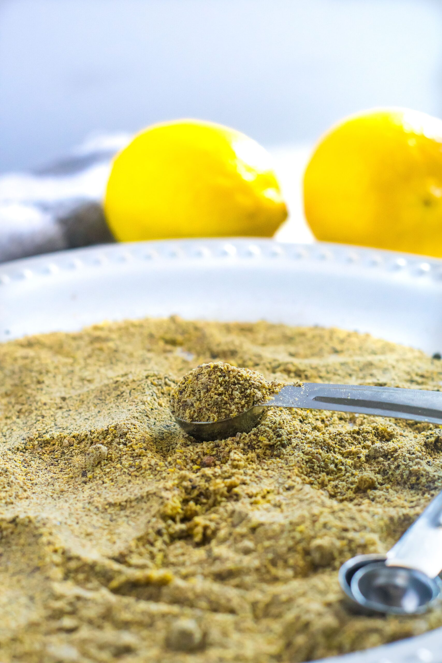homemade lemon pepper seasoning in a teaspoon on a white plate with lemons in the background
