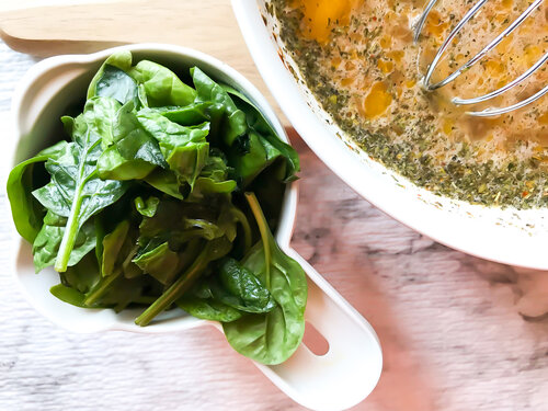 fresh spinach in measuring cup