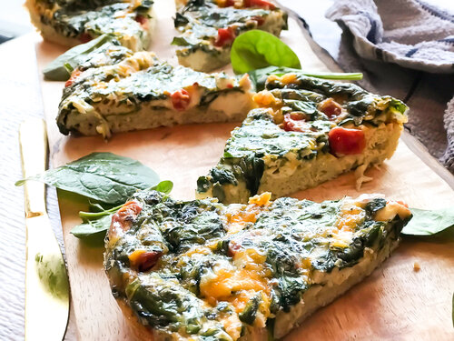 Spinach, Tomato, and Cheddar Frittata on a brown wooden cutting board | Keto, Low-Carb