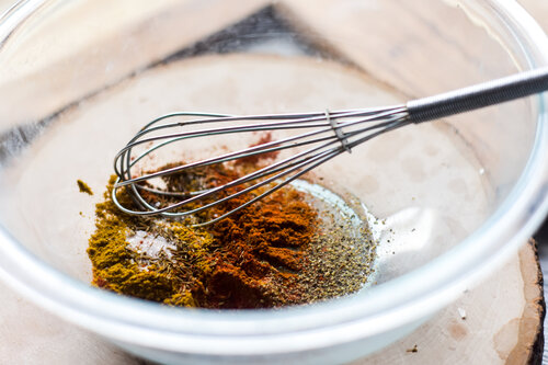 Spices for curry chicken in a glass bowl with whisk