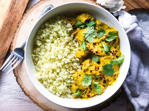 Coconut Curry Chicken with Cauliflower Rice | Keto, Low-Carb in a white bowl on a wooden cutting board
