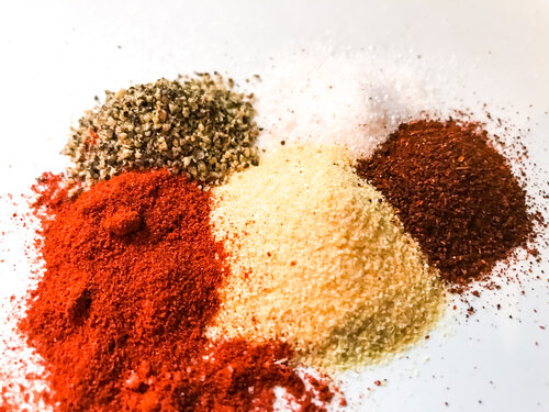 A blend of kosher salt, garlic powder, smoked paprika, chili powder, black pepper, and cayenne seasonings sit atop a plate prepared to be added to homemade blackened ranch dressing.