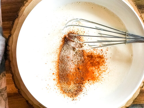 Spices added to the bowl in preparation of a homemade blackened ranch dressing recipe.