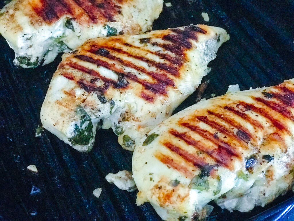 chicken breast being seared in a cast iron grill pan