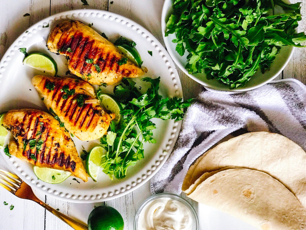 Reverse Seared Tequila Lime Chicken Breasts | Keto, Low-Carb on a white plate atop a white table with limes, cilantro, and arugula.