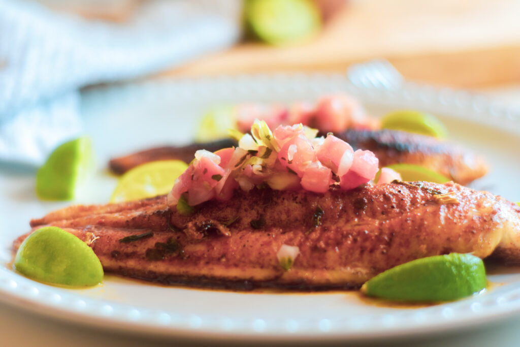 blackened catfish on a white plate with limes