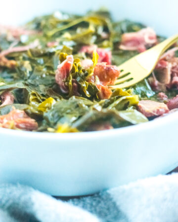 southern style collard greens with ham hocks in white bowl