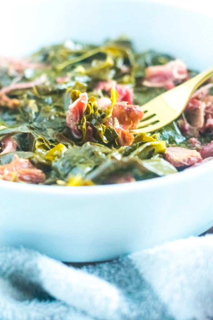 keto southern style collard greens in a white bowl with gold fork