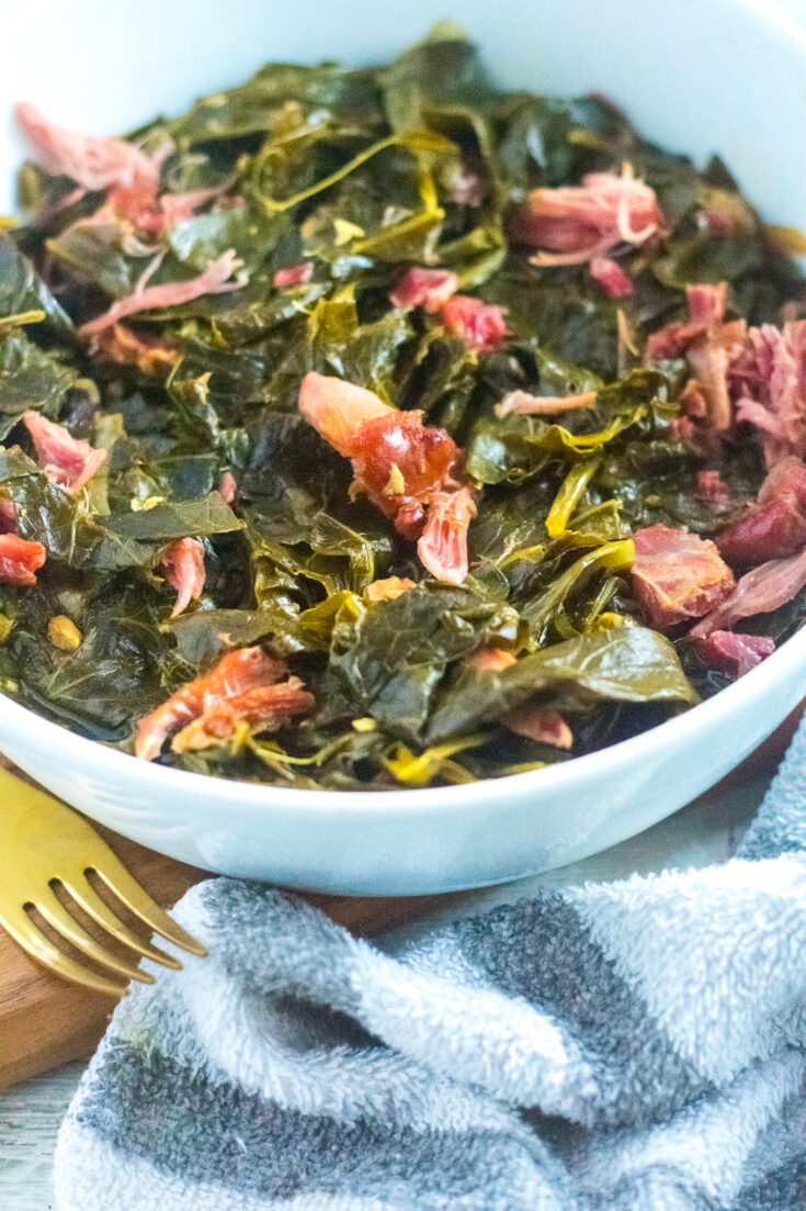 Southern Style Collard Greens with Ham hocks in a white bowl with gold fork