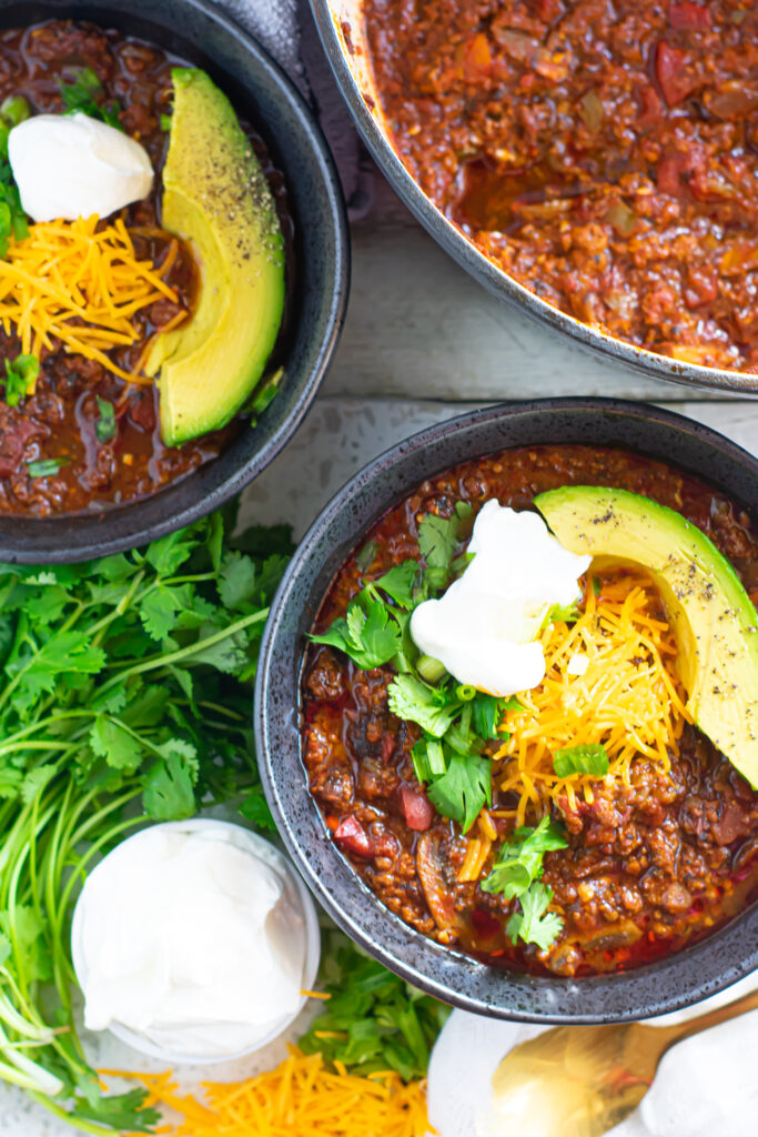 two bowls of chili con carne with toppings
