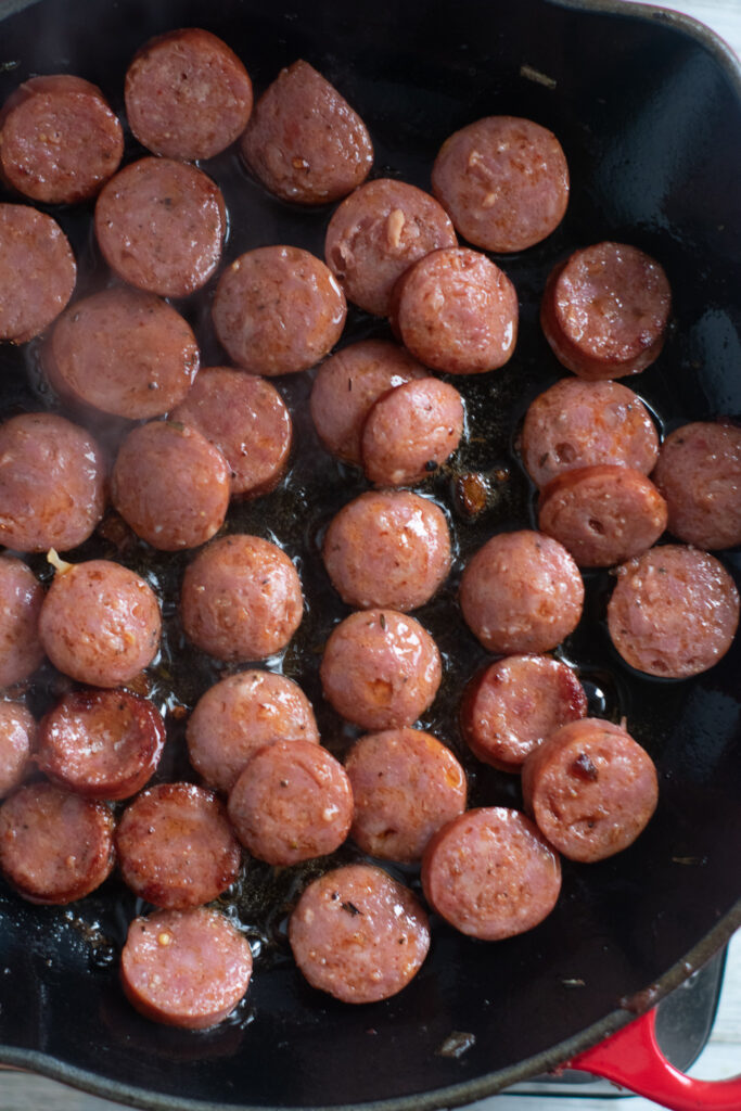 smoked sausage cooking in skillet