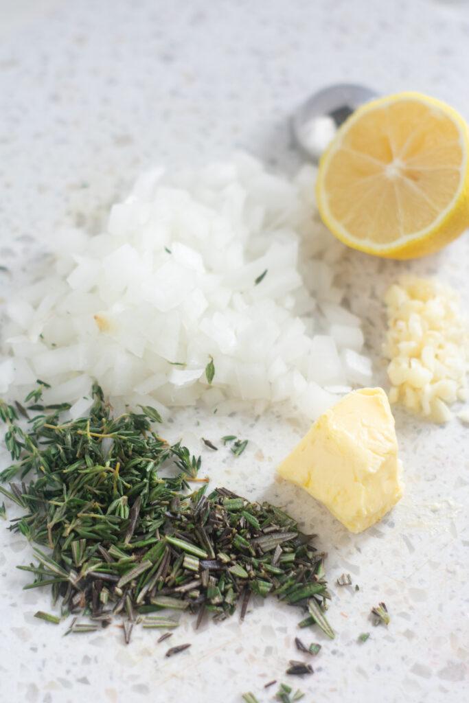 lemon, garlic, herbs, butter, garlic on a white cutting board