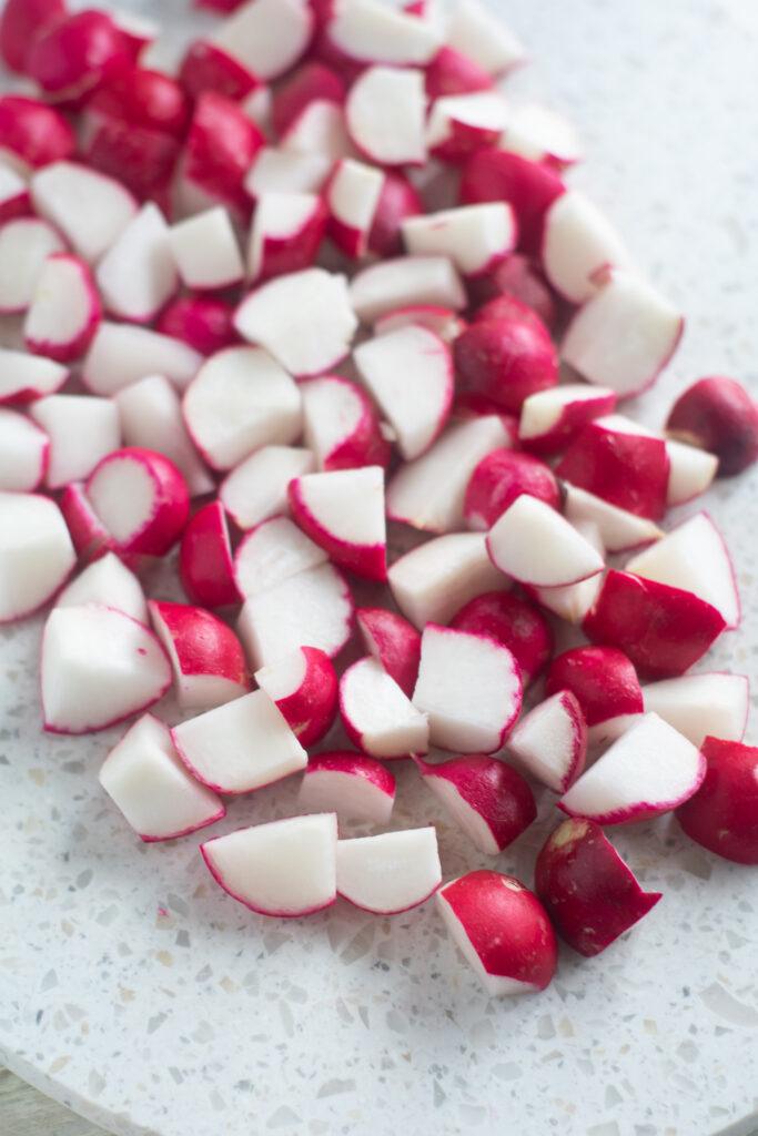 cut radish wedges on white cutting board