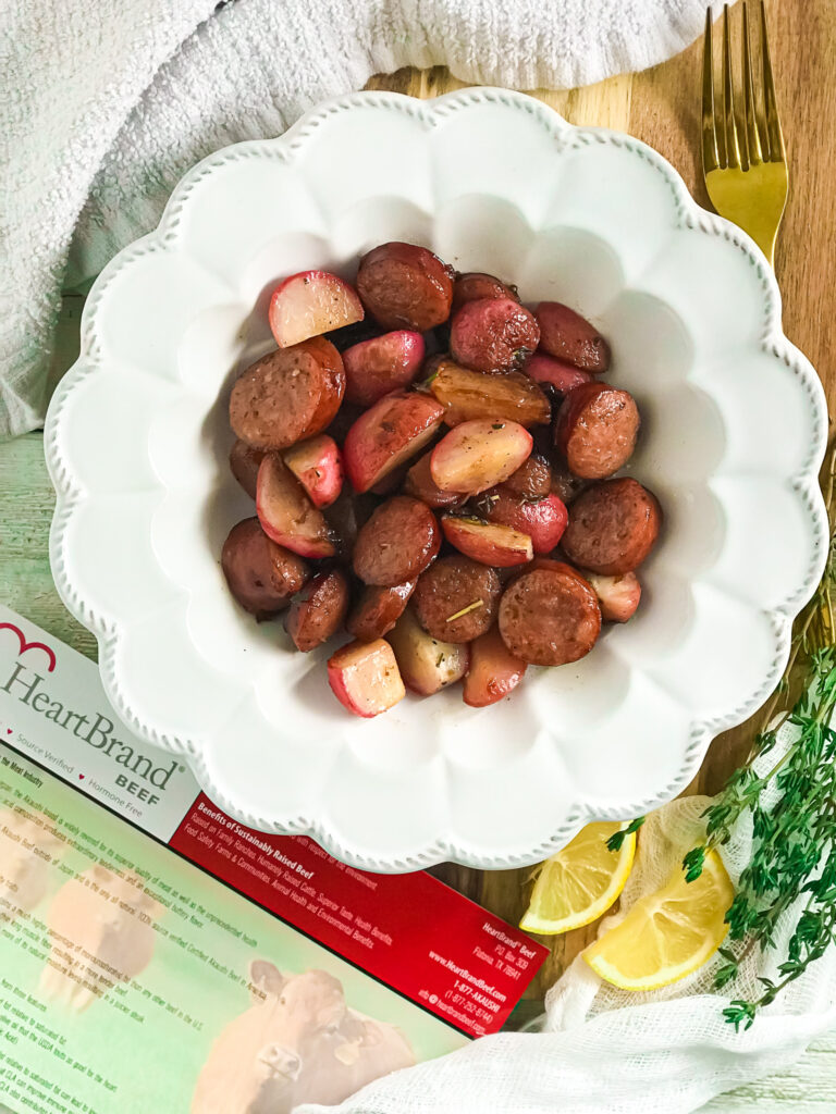 radish wedges and smoked sausage one pan meal tossed in lemon, garlic, butter, and herbs in white bowl
