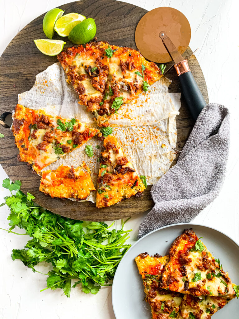 keto-friendly chorizo lime pizza on a brown cutting board with pizza roller