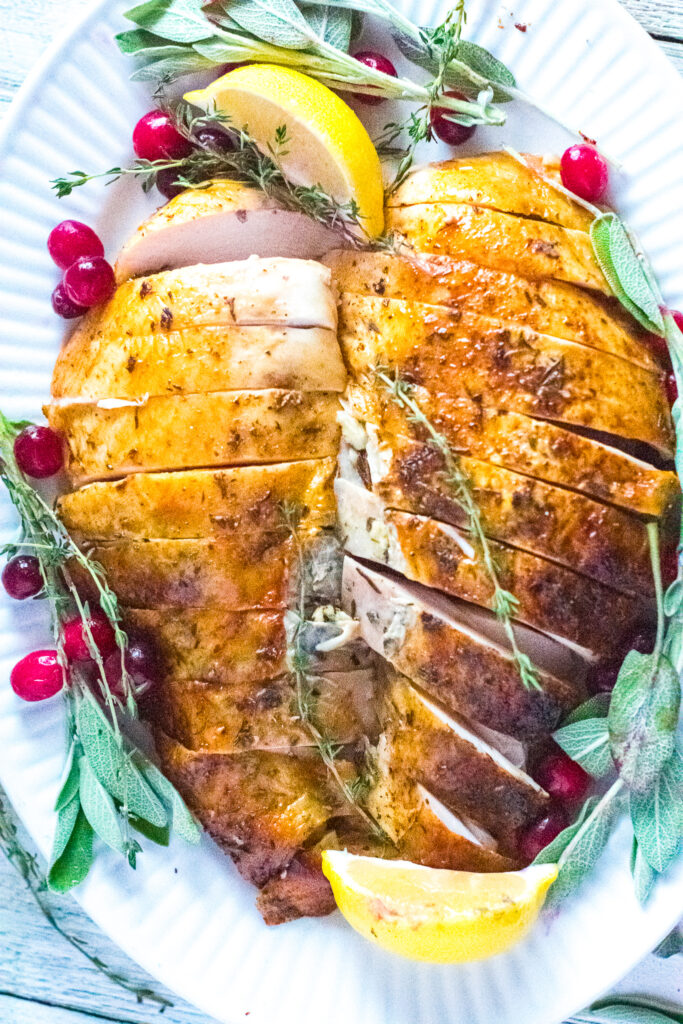 carved turkey on white plate with cranberries, herbs, and lemon wedges.
