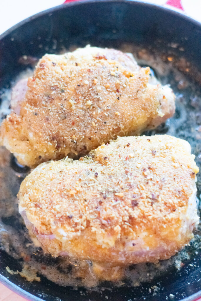 chicken breasts cooking on cast iron pan
