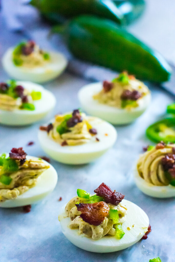 deviled egges topped with bacon and jalapeño pieces, sitting on parchment paper
