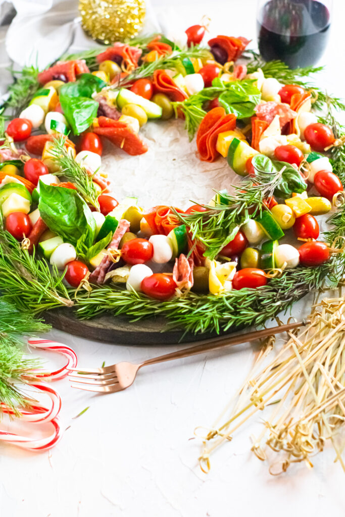 completed antipasto charcuterie wreath on a white background photographed with wine and holiday decorations.