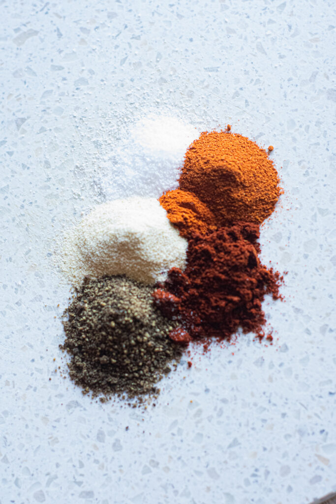 seasonings photographed on a white cutting board.