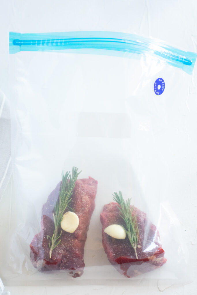 filet mignon, garlic, and rosemary in a plastic bag.