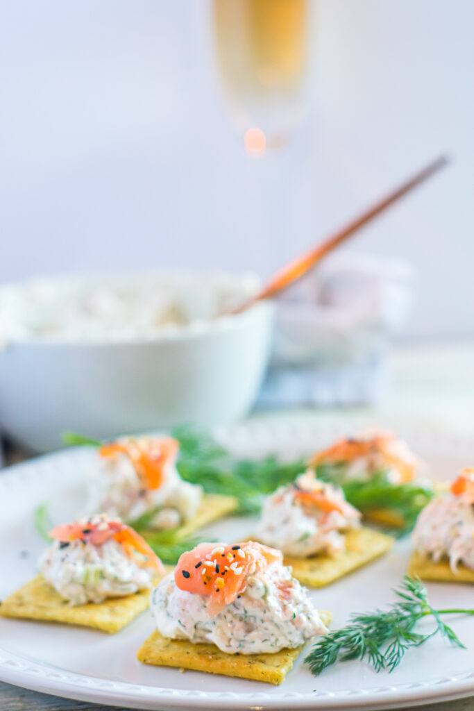Smoked salmon dip served with crackers and fresh dill on a white plate.