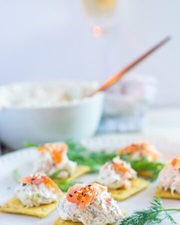Smoked salmon dip with crackers on a white plate with dill garnishment.