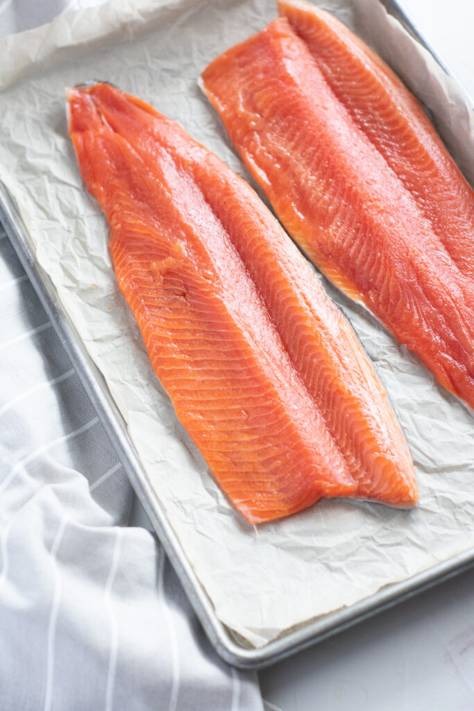 rainbow trout on a parchment paper lined baking sheet.