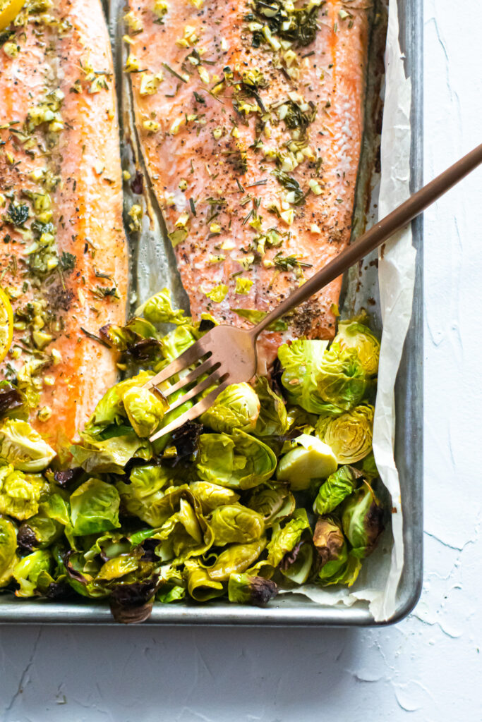 rainbow trout and Brussels sprouts on a sheet pan with a white background.