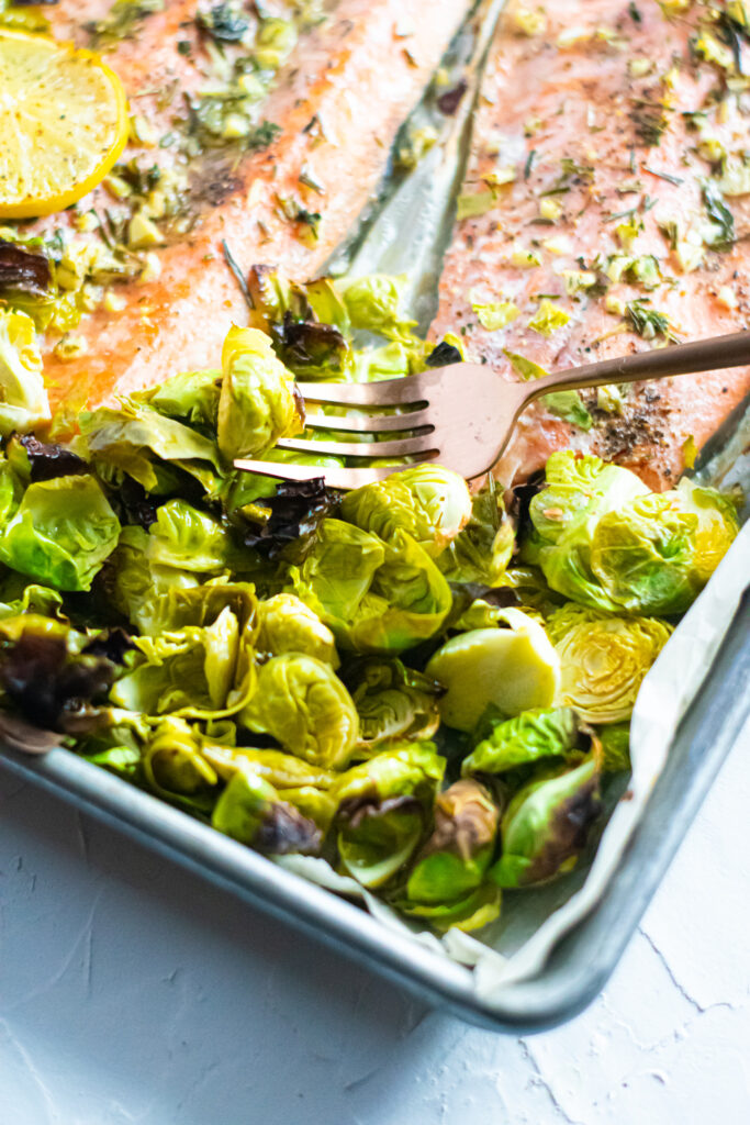 Brussels sprouts on a sheet pan with golden fork. rainbow trout in the background.