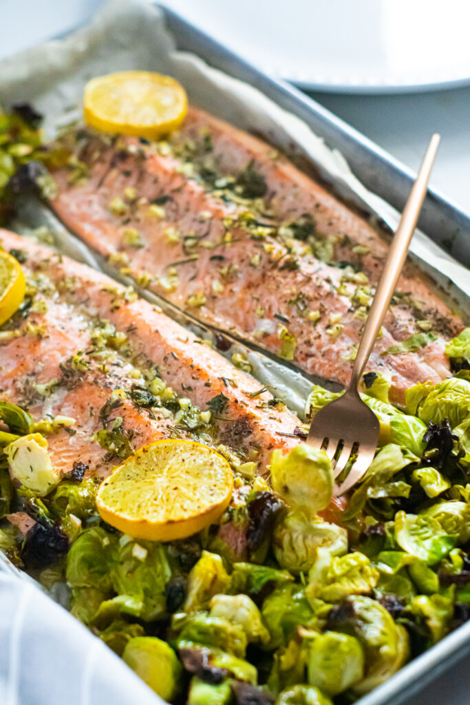 rainbow trout and Brussels sprouts on a sheet pan with a white background. gold fork in foreground.