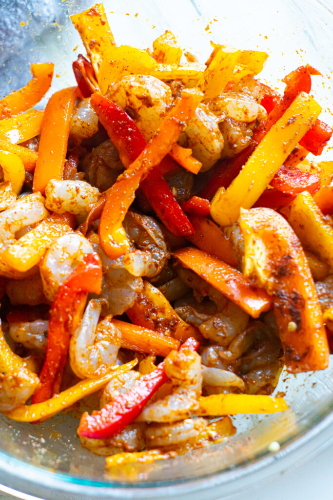 Shrimp, bell pepper strips, and seasoning in a glass mixing bowl.