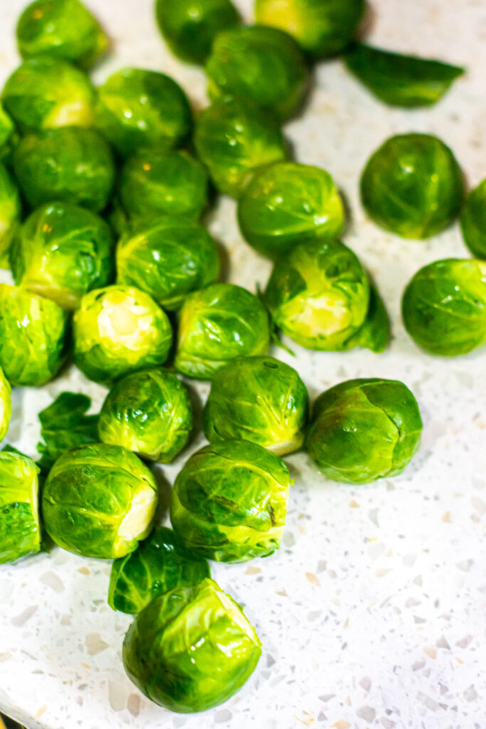 whole Brussels sprouts on a white cutting board.