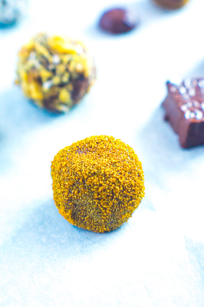 Close up of keto chocolate truffle coated in gold sprinkles.