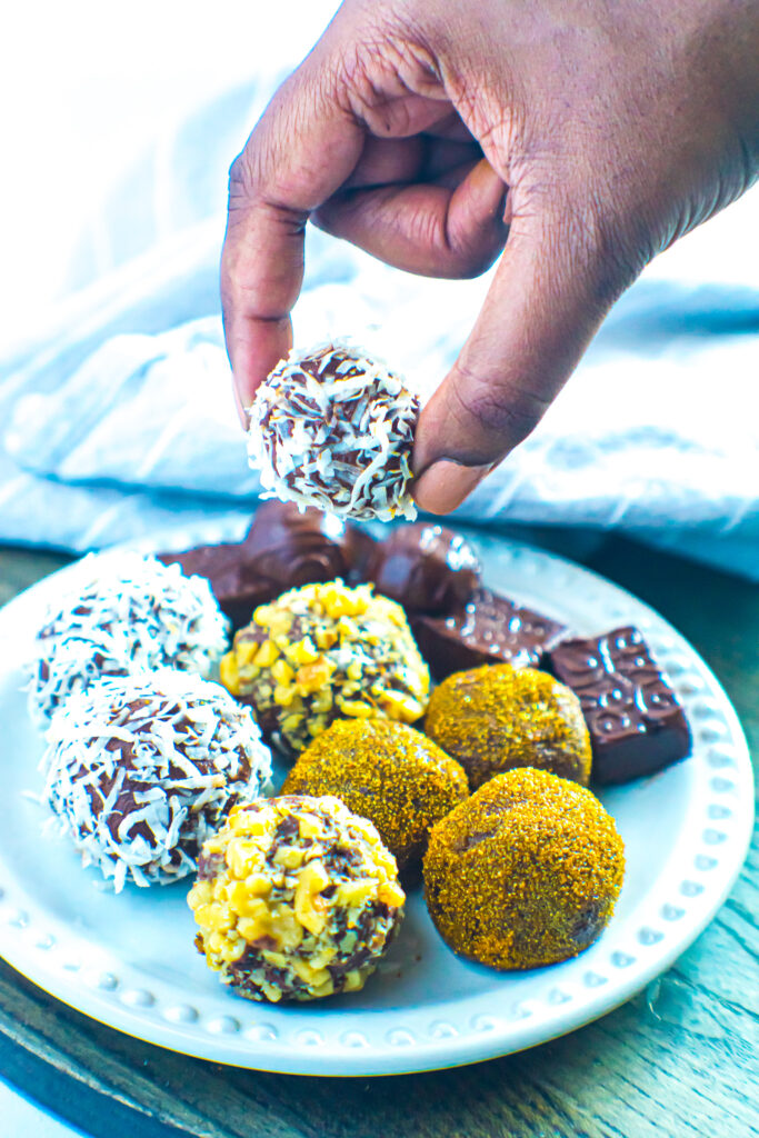 Chocolate truffles on white plate with brown hand holding one of the truffles.