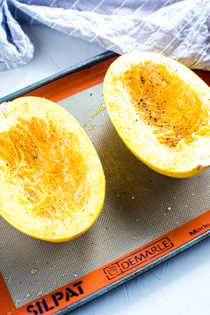 Spaghetti squash seasoned and cut in half on a lined baking sheet.