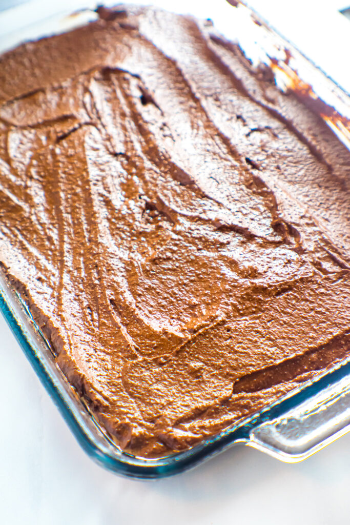 Brownie batter in a glass baking pan.