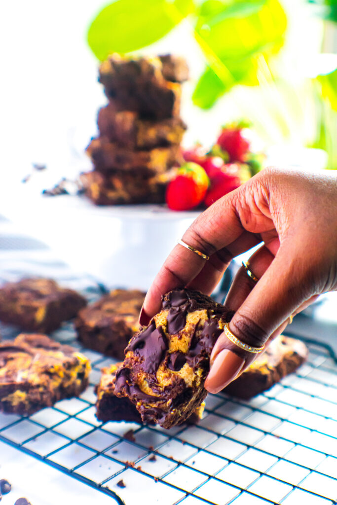 Brown hand holding  a keto-friendly brookie - brownie and chocolate chip cookie bar.