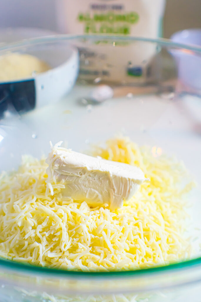 cream cheese and shredded cheese in glass bowl