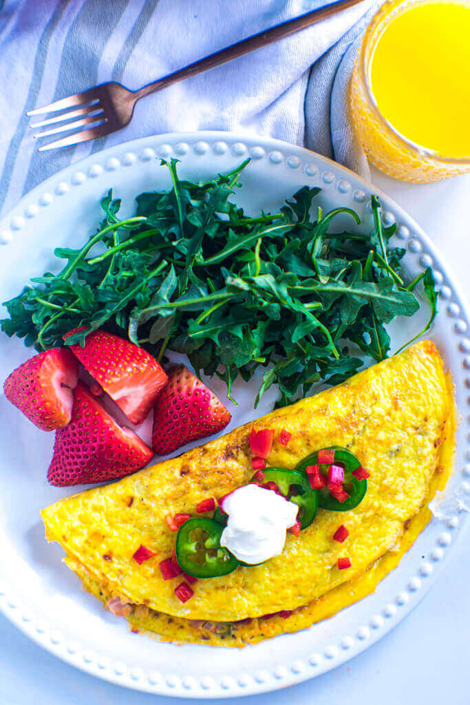Denver omelet on white plate alongside fresh strawberries and arugula. Topped with fresh jalapeno, diced peppers, and sour cream.