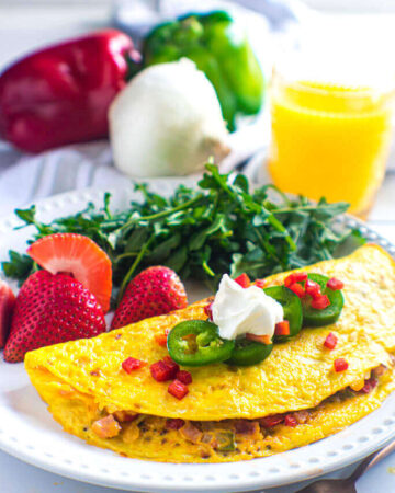 Denver omelet plated with strawberries and arugula. Orange juice and bell peppers are in the background. Omelet is topped with jalapeno, diced red bell pepper, and sour cream.